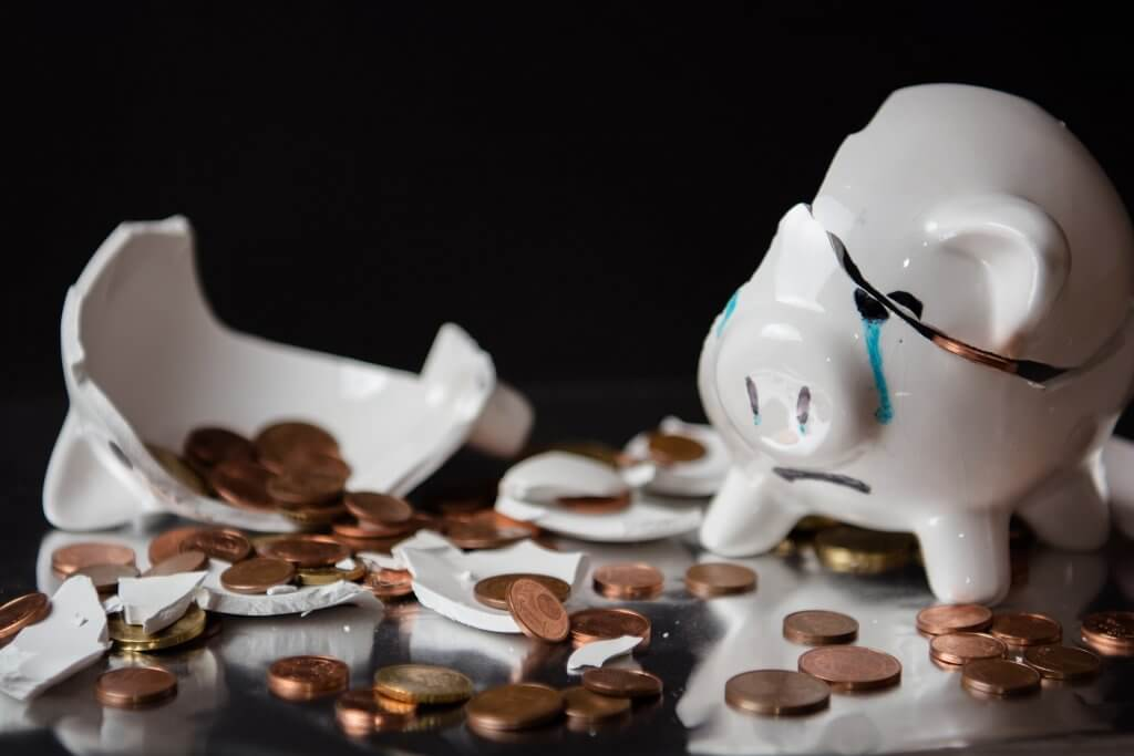 Broken piggy bank with coins spilling out.